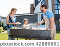 Delighted cheerful man serving meat 42880601