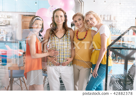 Three loving friends surrounding their pregnant lady 42882378