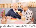 Happy senior woman entertaining husband 42882526