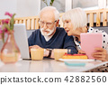 Attentive senior couple booking tickets 42882560