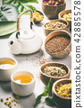 Assortment of dry tea in coconut bowls. 42885578