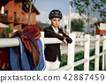 elegant rider woman in helmet with whip 42887459
