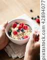 Oatmeal porridge with berries in hands 42894077