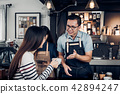 Male barista talking with customer 42894247