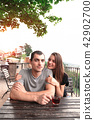 Young beautiful couple share tea at garden table 42902700