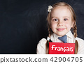 Cute child with book in French language school 42904705