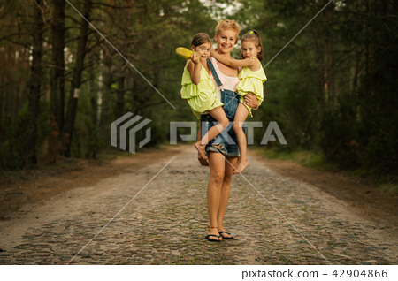 lovely mother holds two small daughters on her way in the woods 42904866