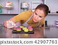 Young appealing confectioner looking at yellow and pink macaroons 42907763