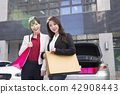 Two attractive young girls are doing shopping with shopping bags, walking and shopping outdoors. 032 42908443