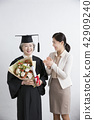 Happy elderly woman wearing graduation robe holding a bouquet celebration with her daughter. 045 42909240