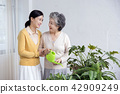 Senior mother and daughter making flower decoration on table. 031 42909249