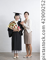 Happy elderly woman wearing graduation robe holding a bouquet celebration with her daughter. 043 42909252