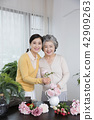 Senior mother and daughter making flower decoration on table. 036 42909263