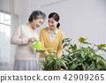 Senior mother and daughter making flower decoration on table. 037 42909265
