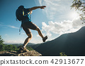Woman hiker walking to the cliff edge  42913677