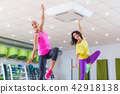 Two young sporty women exercising in fitness studio, dancing, doing cardio, working on balance and 42918138