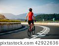 Female cyclist rides a racing bike on road 42922636