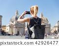Female tourist with a fashinable vintage hipster backpack taking photo of Piazza del Popolo in Rome 42926477