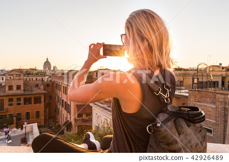 Female tourist taking mobile phone photo of Piazza di Spagna, landmark square with Spanish steps in 42926489
