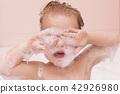 Baby boy rubbing eyes in bath tub. Infant kid in a foam. Close-up portrait. Cute toddler with closed 42926980
