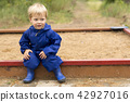 Portrait of toddler child outdoors. Two year old baby boy sitting at playground on the sandbox. Copy 42927016
