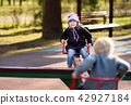Little girl and boy having fun with carousel on outdoor playground 42927184