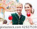 Couple in Bavarian clothes eating candy apples  42927539