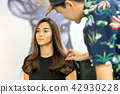 Man hairdresser doing hairstyle for mixed race young women in salon. 42930228