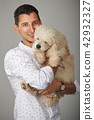 Smiling man holding poodle dog 42932327
