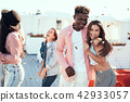 Glad couple entertaining with happy friends 42933057