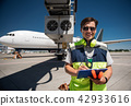 Airport worker looking at camera with smile while writing on clipboard 42933616