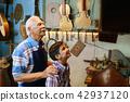 Old Man Grandpa Showing Guitar To Boy Grandson 42937120