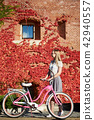Attractive blond girl at pink lady bicycle on sunny day on wall overgrown with red ivy background. 42940557
