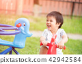 Happy little girl having fun on a playground 42942584
