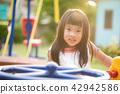 Happy little girl having fun on a playground 42942586