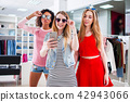 Pretty girls wearing sunglasses fooling around taking selfie showing tongue and horn gestures in 42943066