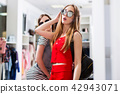 Attractive female models advertising new summer sunglasses collection in fashion store 42943071