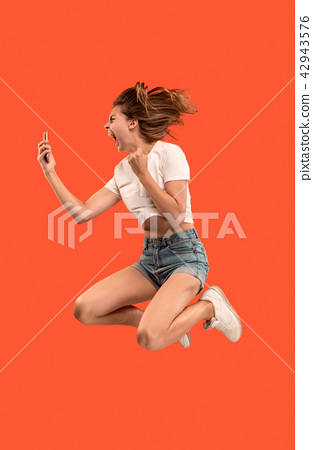 Full length of pretty young woman with mobile phone while jumping 42943576