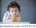 baby boy with porridge on face in time of feeding 42944528