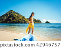 Woman dragging her boat to the water on the beach 42946757