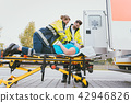 Emergency doctor taking care of seriously injured woman 42946826