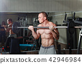 Man practicing with barbell in gym 42946984
