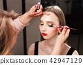 makeup artist applying mascara on a model 42947129