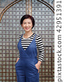 middle aged asian woman smiling in casual clothes 42951391