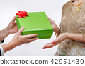Elderly woman receiving a gift from daughter 42951430