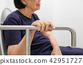 Elderly woman holding on handrail in toilet. 42951727