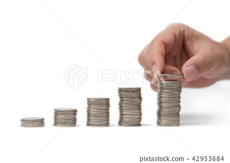 拿著在一枚被堆積的硬幣的手一枚硬幣 42953684