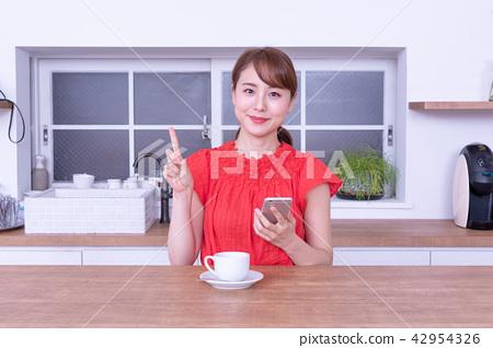 觀看智能手機的婦女,當喝咖啡時 42954326