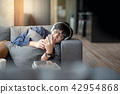 Young Asian man using smartphone relaxing on sofa 42954868