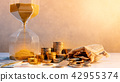 Hourglass and currency on table, Time Investment 42955374